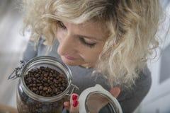 Piękna dziewczyna z kędzierzawym włosy wącha kawowe fasole w szklanym garnku Obrazy Stock