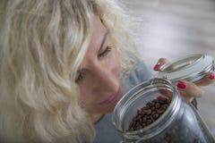 Piękna dziewczyna z kędzierzawym włosy wącha kawowe fasole w szklanym garnku Obraz Royalty Free