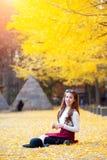 Piękna dziewczyna z kolorów żółtych liśćmi w Nami wyspie, Korea Obraz Stock