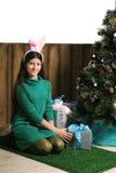 Piękna dziewczyna z królików ucho i dekorującymi prezentów pudełkami jest czekaniem Zdjęcia Royalty Free