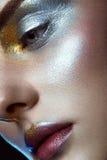 Piękna dziewczyna z kreatywnie złotym i srebnym błyskotliwość makijażem Piękno Twarz obrazy stock