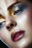 Piękna dziewczyna z kreatywnie złotym i srebnym błyskotliwość makijażem Piękno Twarz zdjęcie stock