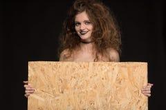 Piękna dziewczyna z makijażem jako czarownica uśmiecha się miejsce dla pisać na czarnym tle i trzyma Zdjęcia Stock