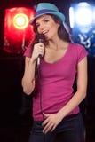 Piękna dziewczyna z mikrofon pozycją w barze Zdjęcia Stock