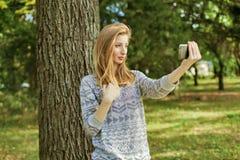 Piękna dziewczyna z niebieskimi oczami robi selfie outdoors zdjęcie stock