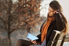 Piękna dziewczyna z pastylka komputerem osobistym sadzającym przy parkiem zdjęcie stock