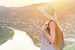 Piękna dziewczyna z plecakiem w kapeluszu spojrzeniach przy i miastem below i rzeką Zdjęcie Stock