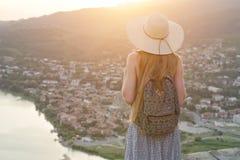 Piękna dziewczyna z plecakiem w kapeluszu spojrzeniach przy i miastem below i rzeką widok z powrotem Zdjęcia Royalty Free