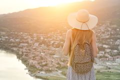 Piękna dziewczyna z plecakiem w kapeluszu spojrzeniach przy i miastem below i rzeką widok z powrotem Obrazy Royalty Free
