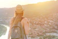 Piękna dziewczyna z plecakiem w kapeluszu spojrzeniach przy i miastem below i rzeką widok z powrotem Obraz Royalty Free
