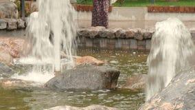 Piękna dziewczyna z smutnymi oczami stoi w deszczu w miasto parku, blisko fontanny zbiory