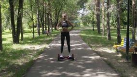 Piękna dziewczyna z sportowym ciałem na hoverboard odprowadzeniu w parku zdjęcie wideo