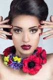 Piękna dziewczyna z wieczór makijażem dalej kwiatami i Obrazy Stock