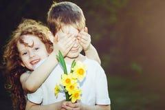 Piękna dziewczyna zakrywa jej chłopaka oczy i chłopiec z bouque zdjęcia stock