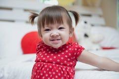 Piękna dziewczynka jest ubranym czerwień uśmiecha się szczęśliwego uśmiech Fotografia Royalty Free