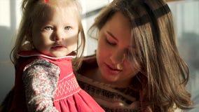 Piękna dziewczynka patrzeje prosto w jej macierzystych rękach z ślicznymi pyzatymi policzkami Uroczy dziecko i jej mama przeciw fotografia royalty free