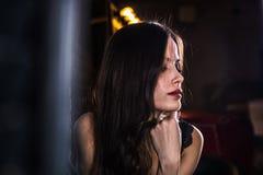 Piękna dziewczyny brunetka w czarnym pokoju z światłem obrazy royalty free