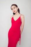 Piękna elegancka azjatykcia kobieta jest ubranym czerwieni suknię na popielatym backgrou Zdjęcia Royalty Free