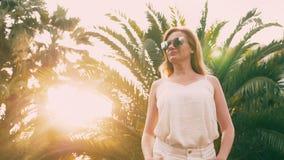 Piękna elegancka blond kobieta w okularach przeciwsłonecznych, chodzi wzdłuż drzewko palmowe ścieżki Palma odbija w szkłach 4K zdjęcie wideo