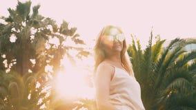 Piękna elegancka blond kobieta w okularach przeciwsłonecznych, chodzi wzdłuż drzewko palmowe ścieżki Palma odbija w szkłach 4K zbiory wideo