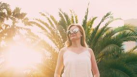 Piękna elegancka blond kobieta w okularach przeciwsłonecznych, chodzi wzdłuż drzewko palmowe ścieżki Palma odbija w szkłach 4K zbiory