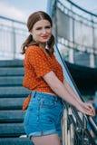 piękna elegancka dziewczyna w drelichu zwiera pozycję na schodkach i ono uśmiecha się obraz royalty free