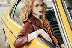 piękna elegancka dziewczyna w skórzanej kurtki obsiadaniu w staromodnym samochodzie i patrzeć zdjęcie stock