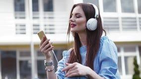 Piękna elegancka kobieta słucha muzyka na jej telefonie komórkowym z hełmofonami, zamyka ona i śpiewa along, oczy, gestykuluje zbiory wideo