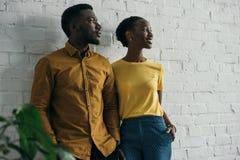 piękna elegancka młoda amerykanin afrykańskiego pochodzenia para stoi blisko białej ściany z cegieł zdjęcie stock