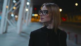 Piękna elegancka młoda kobieta w szkłach z czarnymi obręcza i zmroku ubraniami chodzi blisko centrum biznesu w zdjęcie wideo