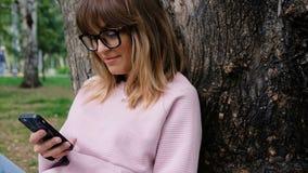 Piękna emocjonalna młoda dziewczyna używa telefon komórkowego Żeński patrzejący uśmiech i kamerę Modniś młodej kobiety używać zbiory wideo