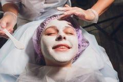 Piękna europejska kobieta ma twarzową skóry procedurę stosować białą odmładzanie maskę cosmetologist zdjęcie royalty free