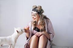 Piękna europejska kobieta z jej psem w białym mieszkaniu, europejska kobieta bawić się z jej białym psem, ładna kobieta zdjęcie royalty free
