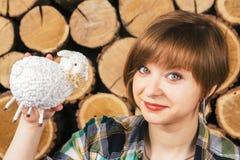 Piękna europejska z włosami dziewczyna pokazuje jagnięcego zakończenie na drewnianym tle Fotografia Stock
