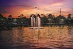 Piękna fontanna nad sylwetka jawnym parkiem przed półmrokiem Obraz Royalty Free