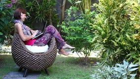 Piękna freelancer kobieta pracuje na komputerze przy jej willą z zielonym tropikalnym ogródem bali piękny Indonesia wyspy kuta mę zdjęcie wideo