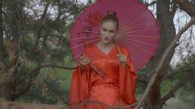 Piękna gejsza w czerwonym kimonie z parasolem na jej ramieniu ciągnie tanto od swój scabbard i spojrzenia w zbiory wideo