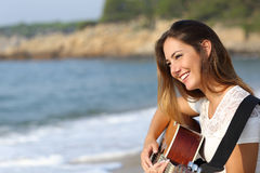 Piękna gitarzysta kobieta bawić się gitarę na plaży Fotografia Royalty Free