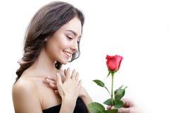 Piękna gniewna dziewczyna otrzymywa jeden czerwieni róży Patrzeje ono uśmiecha się i kwiaty zaskakuje, Zdjęcie Royalty Free