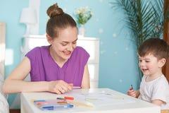 Piękna gospodyni domowa w przypadkowej purpur t koszula wydaje czas wolnego z jej małym synem, use kolorowi markiery dla rysować  zdjęcia stock