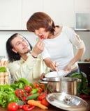 Piękna gospodyni domowa z mężczyzna kucharstwem z świeżymi warzywami przy ho Obrazy Royalty Free