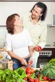 Piękna gospodyni domowa z mężczyzna kucharstwem z świeżymi warzywami przy ho Zdjęcia Stock