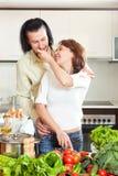 Piękna gospodyni domowa z mężczyzna kucharstwem z świeżymi warzywami przy ki Obrazy Royalty Free