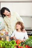 Piękna gospodyni domowa z mężczyzna kucharstwem z świeżymi warzywami w ki Obraz Stock