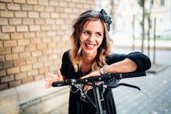piękna i atrakcyjna uśmiechnięta kobieta z nowożytnego miasto transportu elektryczną hulajnoga zdjęcia stock