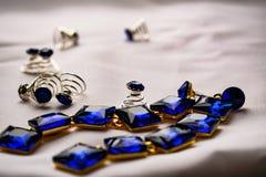Piękna i modna biżuteria i akcesoria dla kobiet Szafirowi kolczyki z kwadratowymi kamieniami na białym tekstylnym tle Błękitny zdjęcie stock