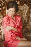 Piękna i seksowna brunetka modela dziewczyna w peignoir, pozuje na kanapie przy luksusowym wnętrzem Zdjęcia Stock