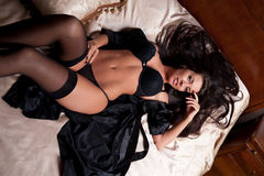 Piękna i seksowna brunetki młoda kobieta jest ubranym czarną bieliznę w łóżku. Moda krótkopędu bielizna salowa. Seksowna młoda dzi Zdjęcia Stock