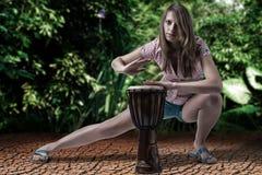 Piękna blondy kobieta bawić się djembe bęben Fotografia Stock