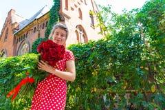 Piękna i seksowna dziewczyna trzyma bukiet czerwone róże na tle stary czerwień kasztel fotografia stock